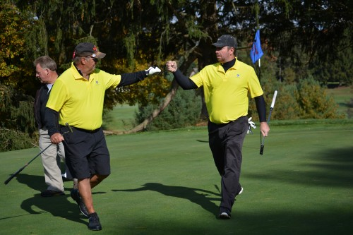 Partners Joe Hughes and Whit Cook celebrate a hole win in Alternate Shot.